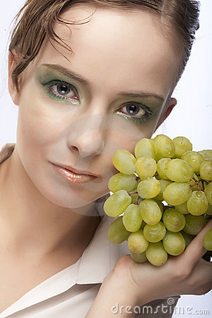 Attractive woman with bunch of grapes