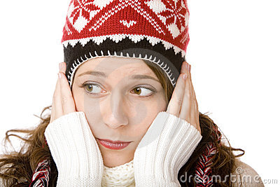 Attractive woman with cap and scarf holding cheeks