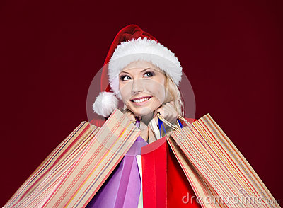 Attractive woman in Christmas cap hands packets