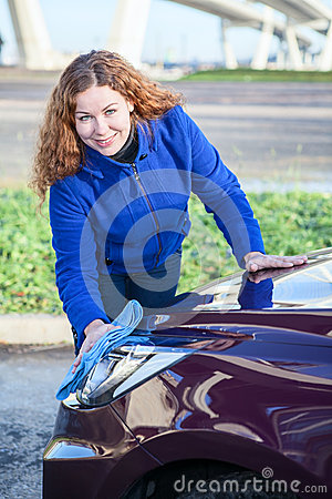 Attractive woman cleaning car