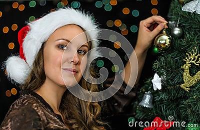 Attractive woman decorates tree