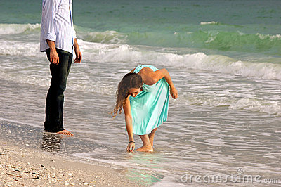 Attractive woman in dress stoops to pick up shell