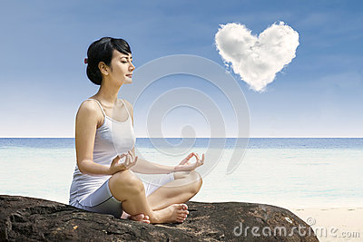 Attractive woman exercise yoga under love cloud at beach