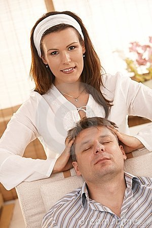 Attractive woman giving head massage to man