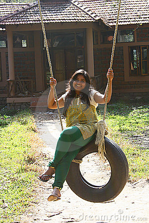 Attractive Woman having fun on tire swing