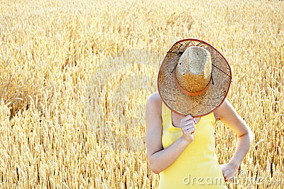 Attractive woman hiding behind her hat