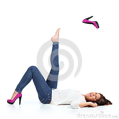 Attractive woman with jeans  throwing a fuchsia heel