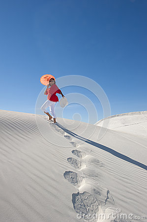 Attractive woman leaving footsteps up a sanddune