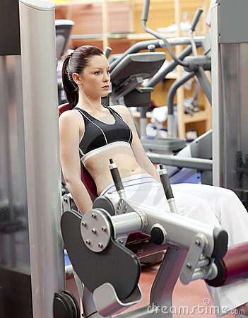 Attractive woman lifting weights with a leg press