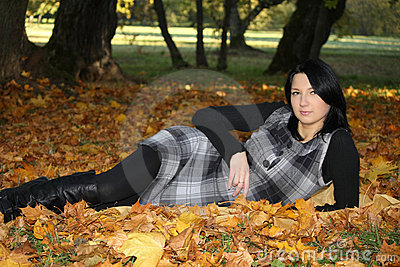 Attractive woman lying on yellow leafage