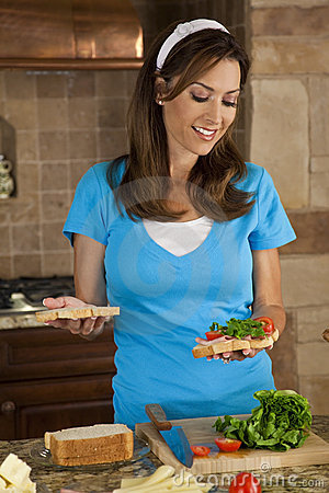 Attractive Woman Making Sandwiches In Home Kitchen