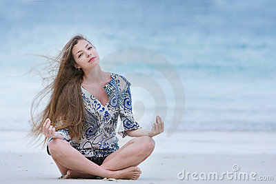 Attractive woman meidtating on sea background