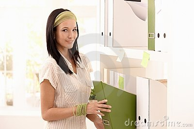 Attractive woman packing folders on shelf