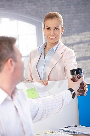 Attractive woman passing coffee to colleague