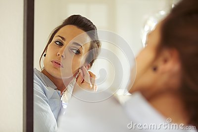 Attractive woman putting on her earrings