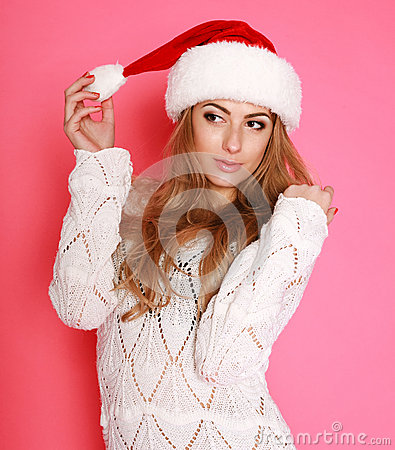 Attractive woman in santa hat, in studio on pink