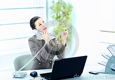 Attractive woman sitting at desk at work on landline phone call,