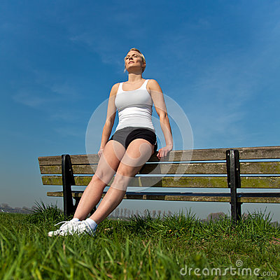 Attractive woman in sports wear taking a break