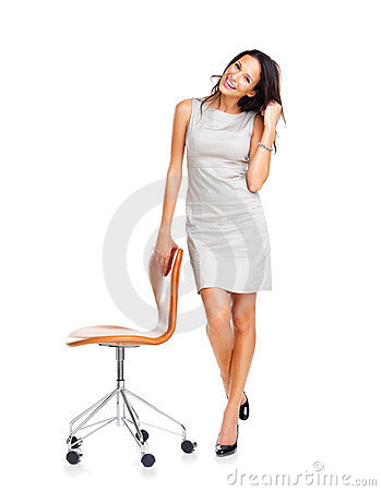 An attractive woman standing with a chair
