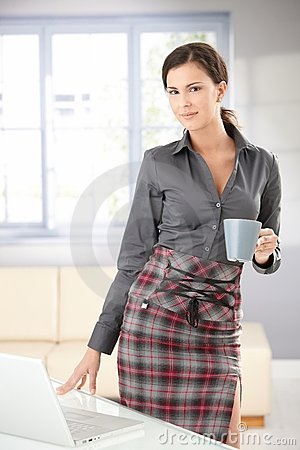 Attractive woman standing drinking tea