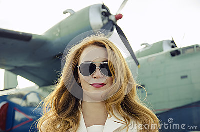 Attractive woman in sunglasses outside near military plane