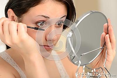 Attractive woman using mascara and handheld mirror