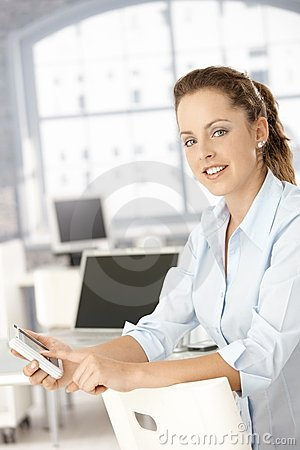 Attractive woman using mobile in office smiling
