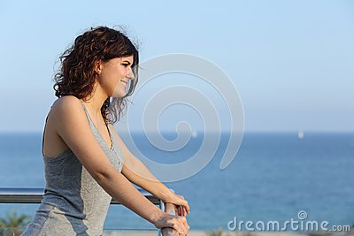 Attractive woman watching the sea from a balcony