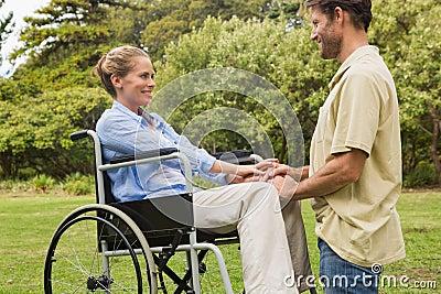 Attractive woman in wheelchair with partner kneeling beside her
