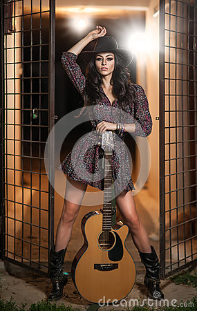 Free Attractive Woman With Country Look, Indoors Shot, American Country Style. Girl With Black Cowboy Hat And Guitar Stock Image - 66852381
