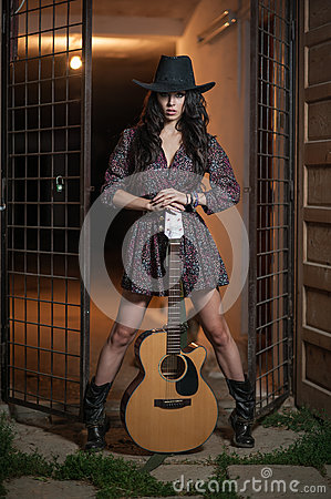 Free Attractive Woman With Country Look, Indoors Shot, American Country Style. Girl With Black Cowboy Hat And Guitar Royalty Free Stock Photography - 82205187