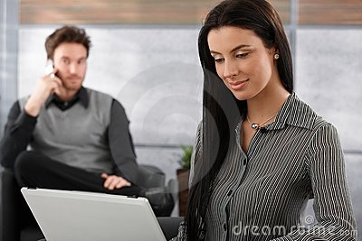 Attractive woman working on laptop smiling Stock Photo