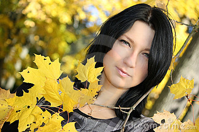 Attractive woman with yellow leafage