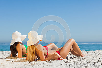 Attractive women in bikinis sunbathing