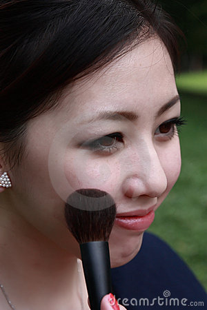 Attractive young adult woman applying blusher