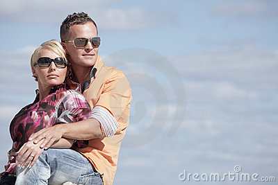 Attractive young couple on a cloudy sky background