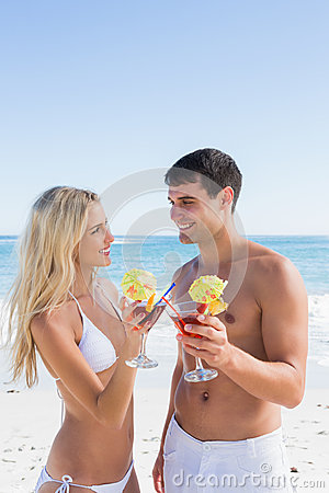 Attractive young couple holding cocktails