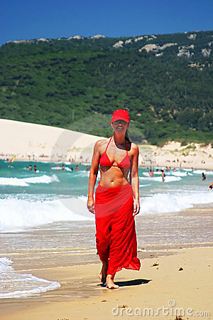 Attractive young girl in red sarong, bikini and baseball cap walking along crowded white sandy beach