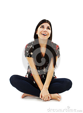 Attractive young girl sitting on the floor looking up