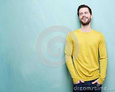 Attractive young man laughing against blue background