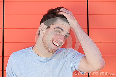 Attractive young man smiling with hand in hair