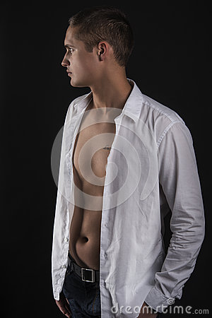 Sensual young man in white shirt standing in profile