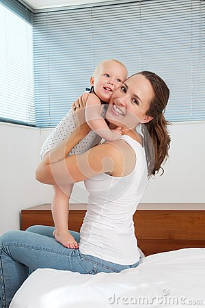 Attractive young mother holding cute baby in bedroom