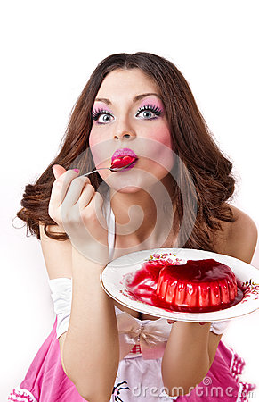 Attractive young satisfied woman eating pudding