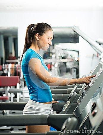 Attractive young woman adjusts the treadmill