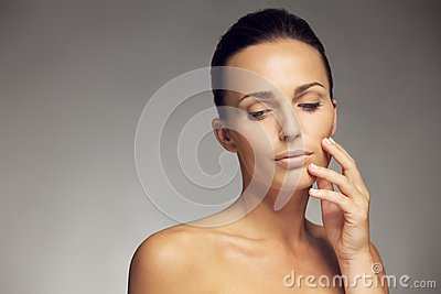 http://thumbs.dreamstime.com/x/attractive-young-woman-beautiful-skin-close-up-portrait-brunette-holding-hand-face-looking-down-33865172.jpg