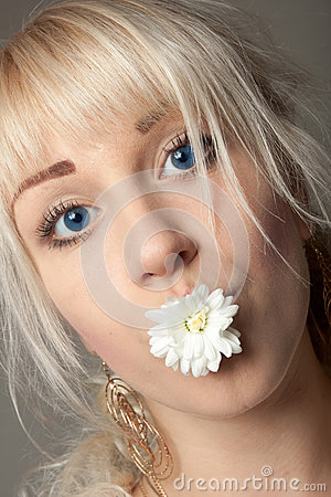 Attractive young woman with big blue eyes and a chrysanthemum in her mouth