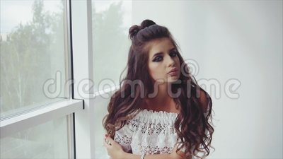 Attractive young woman brunette posing sitting near the window. Slow motion stock footage