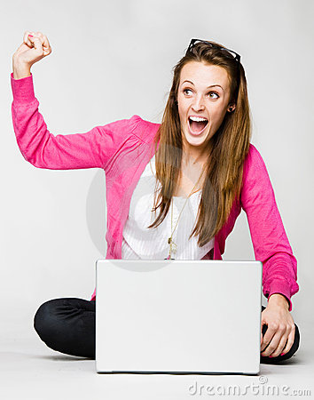 Attractive young woman celebrating with laptop
