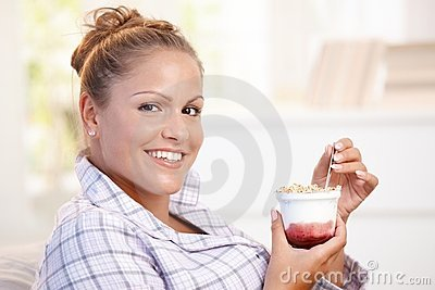 Attractive young woman eating yoghurt at home
